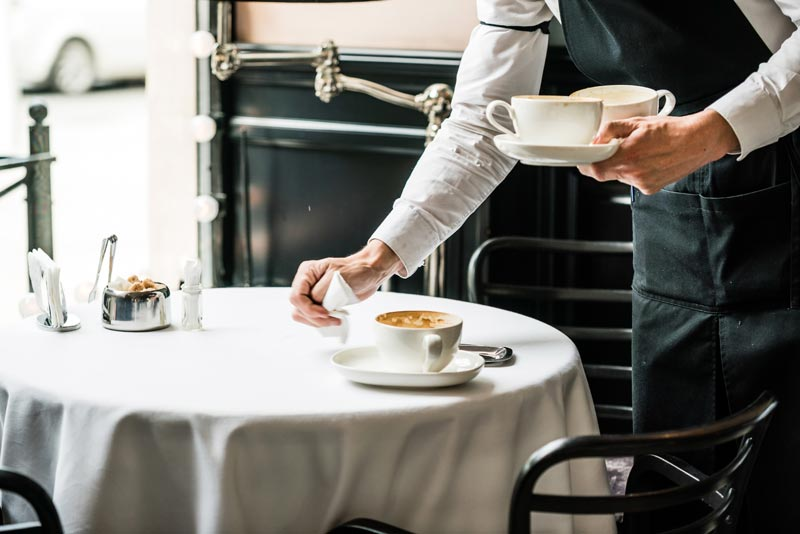 Waiter placing cup of coffee on table